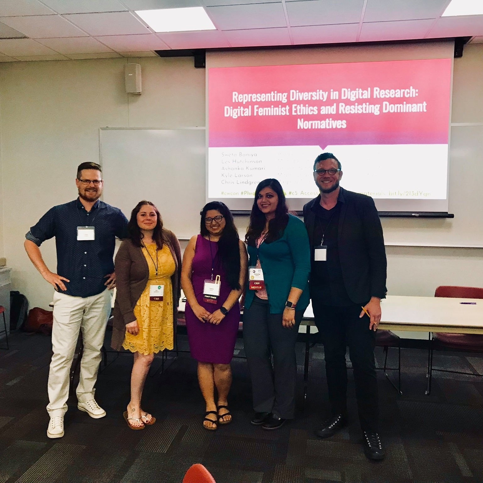Computers and Writing 2018 - Pictured here (left to right): Chris Lindgren, Les Hutchinson, Sweta Baniya, Ashanka Kumari, and Kyle Larson stand in front of a projector screen displaying their opening powerpoint slide for their Computers and Writing Roundtable on representing diversity in digital research. Baniya, Sweta, Les Hutchinson, Ashanka Kumari, Kyle Larson, and Chris Lindgren.