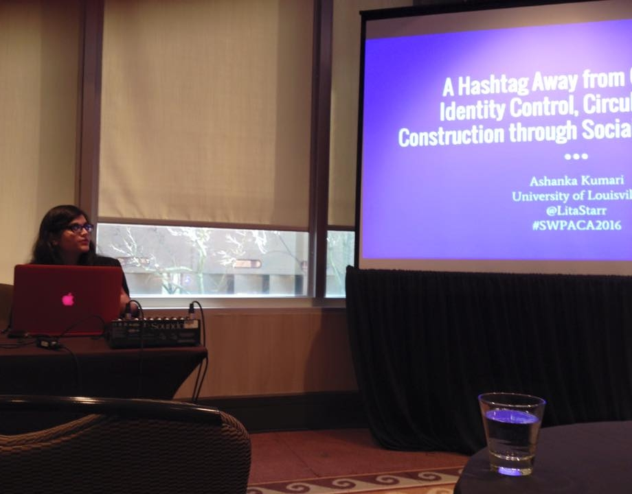 "Southwest Popular/American Culture Studies Conference - Pictured here: Ashanka Kumari (sitting behind a table) presents her paper about identity control, circulation, and construction at the 2016 Southwest Popular/American Culture Studies Conference.Kumari, Ashanka. ""A Hashtag Away from Celebrity: Identity Control, Circulation, and Construction through Social Media Spaces."" Paper. Southwest Popular/ American Culture Studies Conference. Albuquerque, New Mexico. February 2016."
