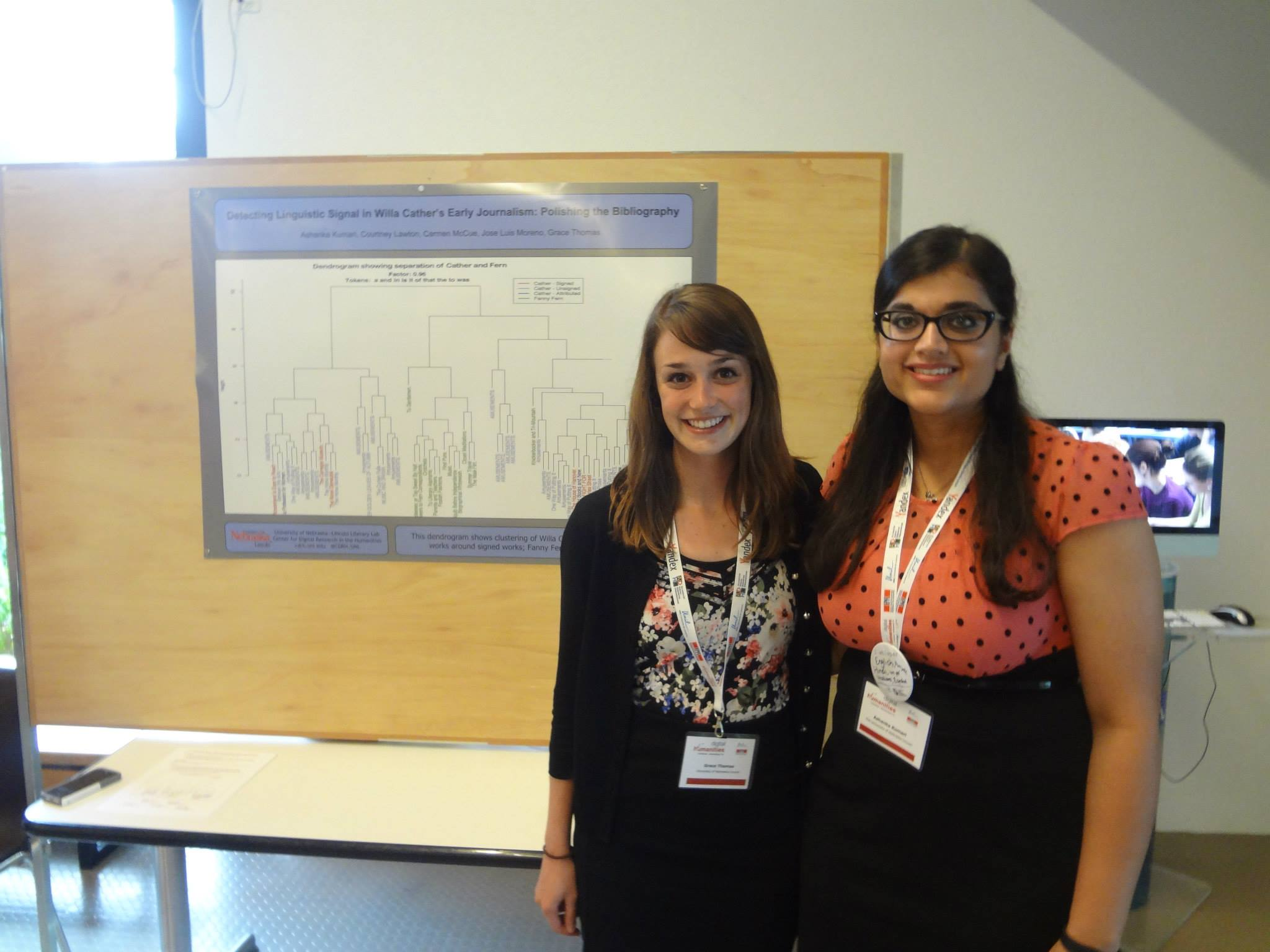 "Digital Humanities 2014 - Pictured here (left to right) Grace Thomas and Ashanka Kumari pose in front of their poster on detecting linguistic signal in Willa Cather's Early Journalism at the Digital Humanities 2014 conference.Kumari, Ashanka, Courtney Lawton, Carmen McCue, Joseba Moreno, and Grace Thomas. ""Detecting Linguistic Signal in Willa Cather's Early Journalism: Polishing the Bibliography."" Poster. Digital Humanities 2014. Lausanne, Switzerland. July 2014."