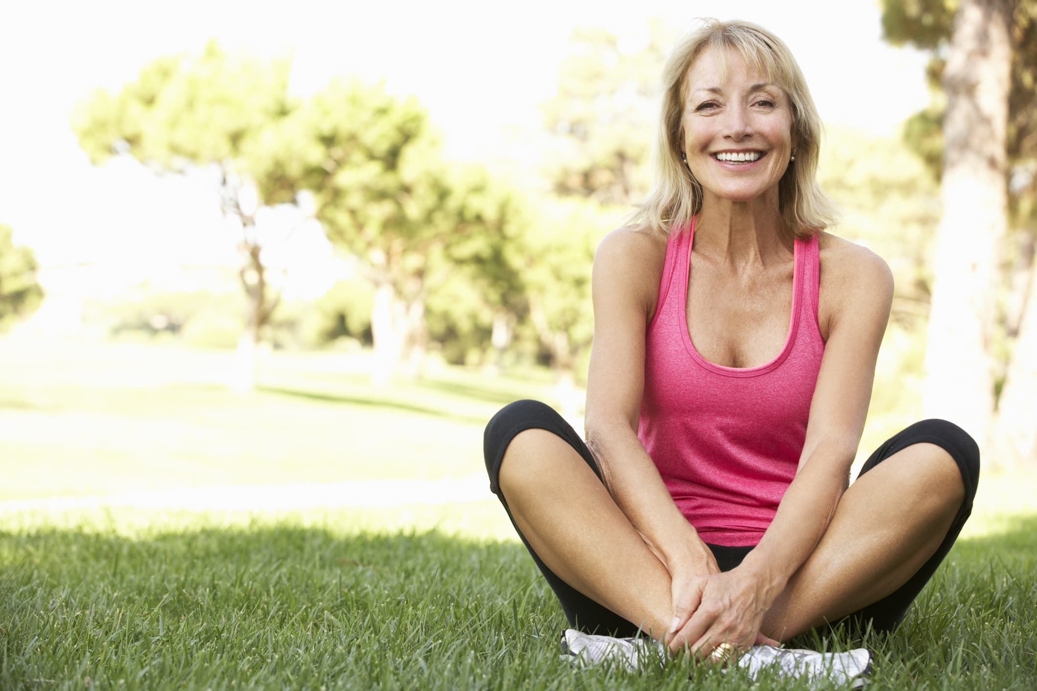 woman sitting on grass outside smiling