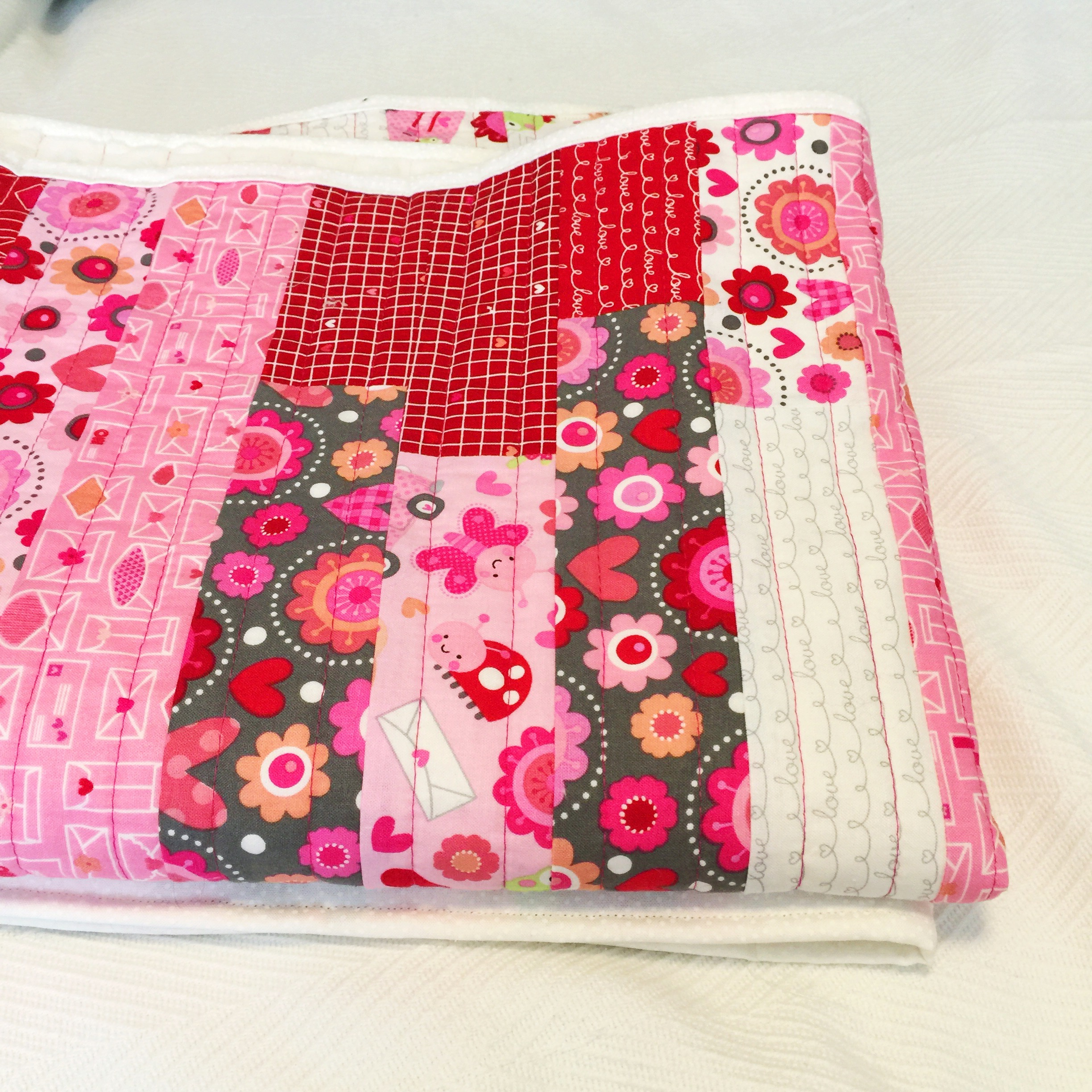 jelly roll baby quilt using Doodlebug for Riley Blake Lovebug collection fabric