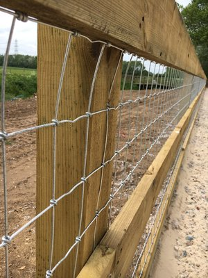 Using a wooden top rail is a safer option for horses and humans as shown at this equine construction.