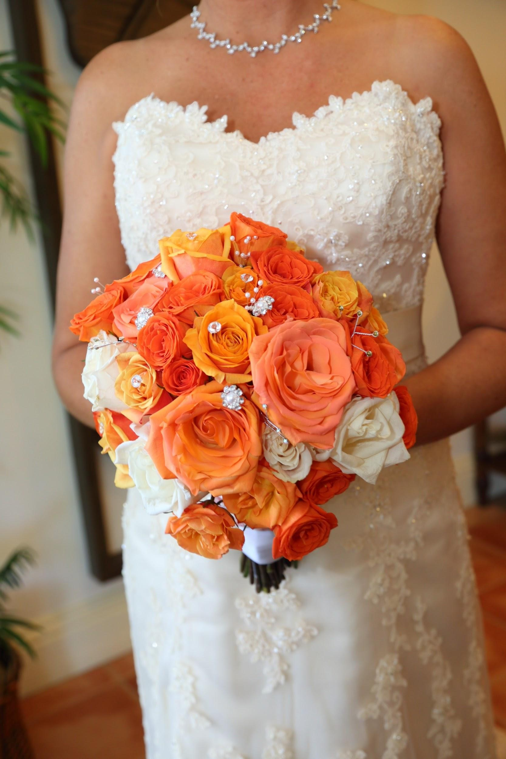 Lush peach and white roses with rhinestone accents for the bride