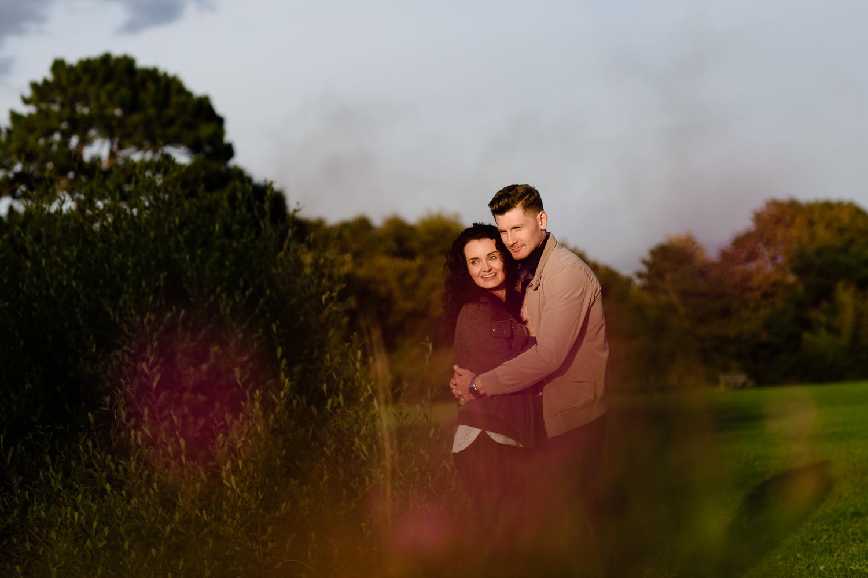 Couple having a hug shot through pink flowers at sunset