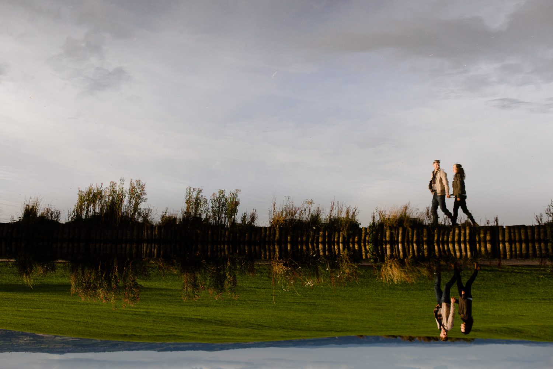 Flipped reflection of a couple walking alongside a lake - Merseyside wedding photography