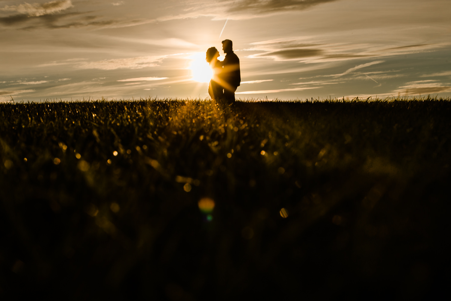 Starburst sunset with silhouette couple on a hill - Merseyside golden hour couple shoot
