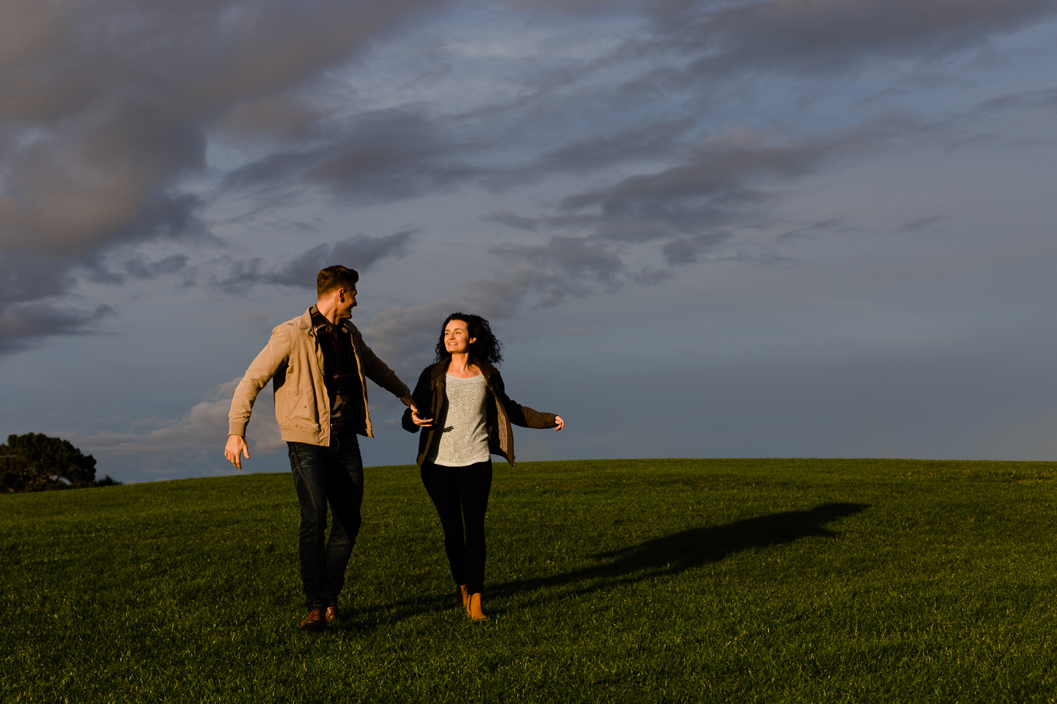 A couple running down a hill - Fun pre wedding shoot in Wirral Country Park, Merseyside