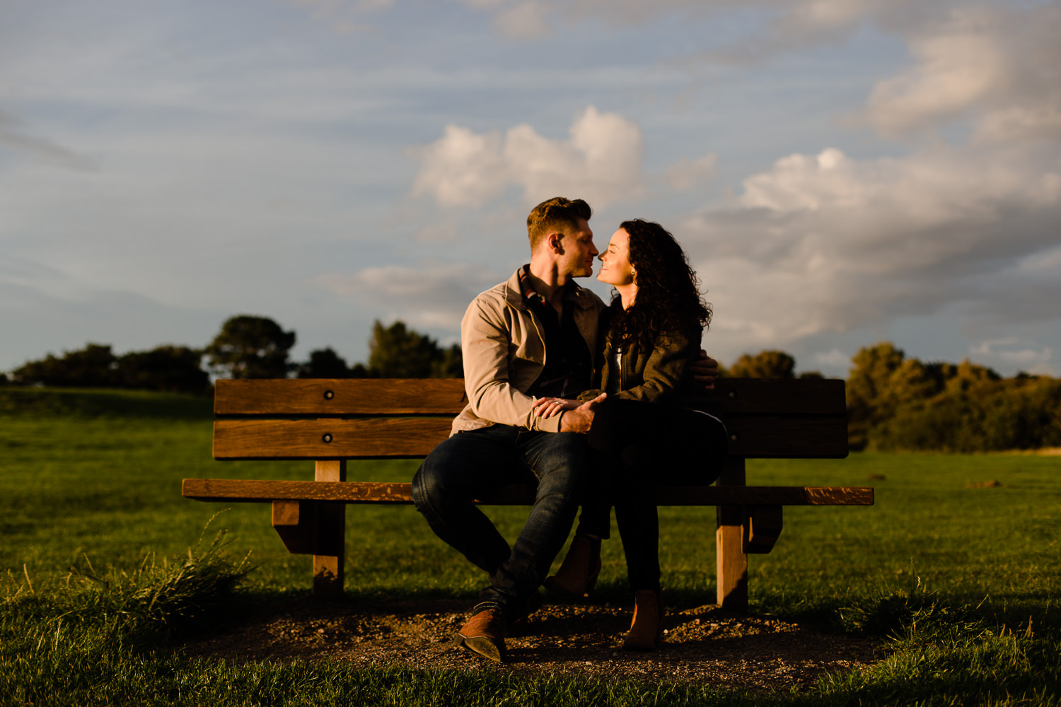 A couple close together on a bench at sunset