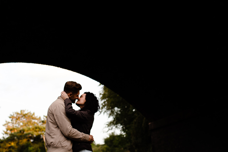 A couple kiss under a bridge
