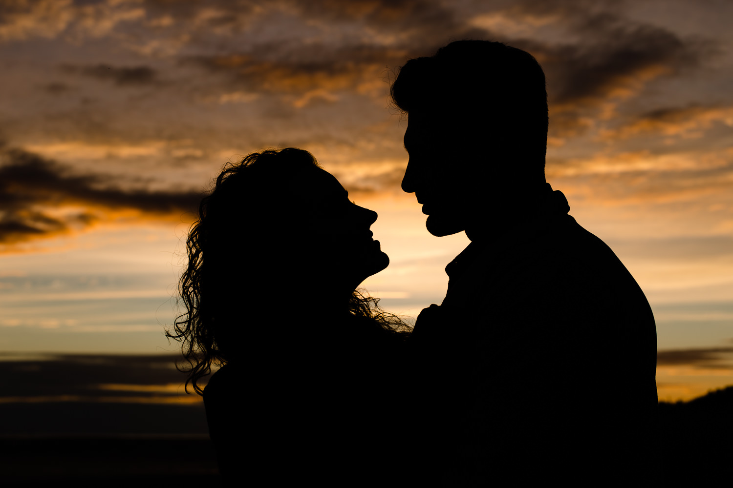 Couples silhouette against the colourful sunset sky - Wirral Country Park