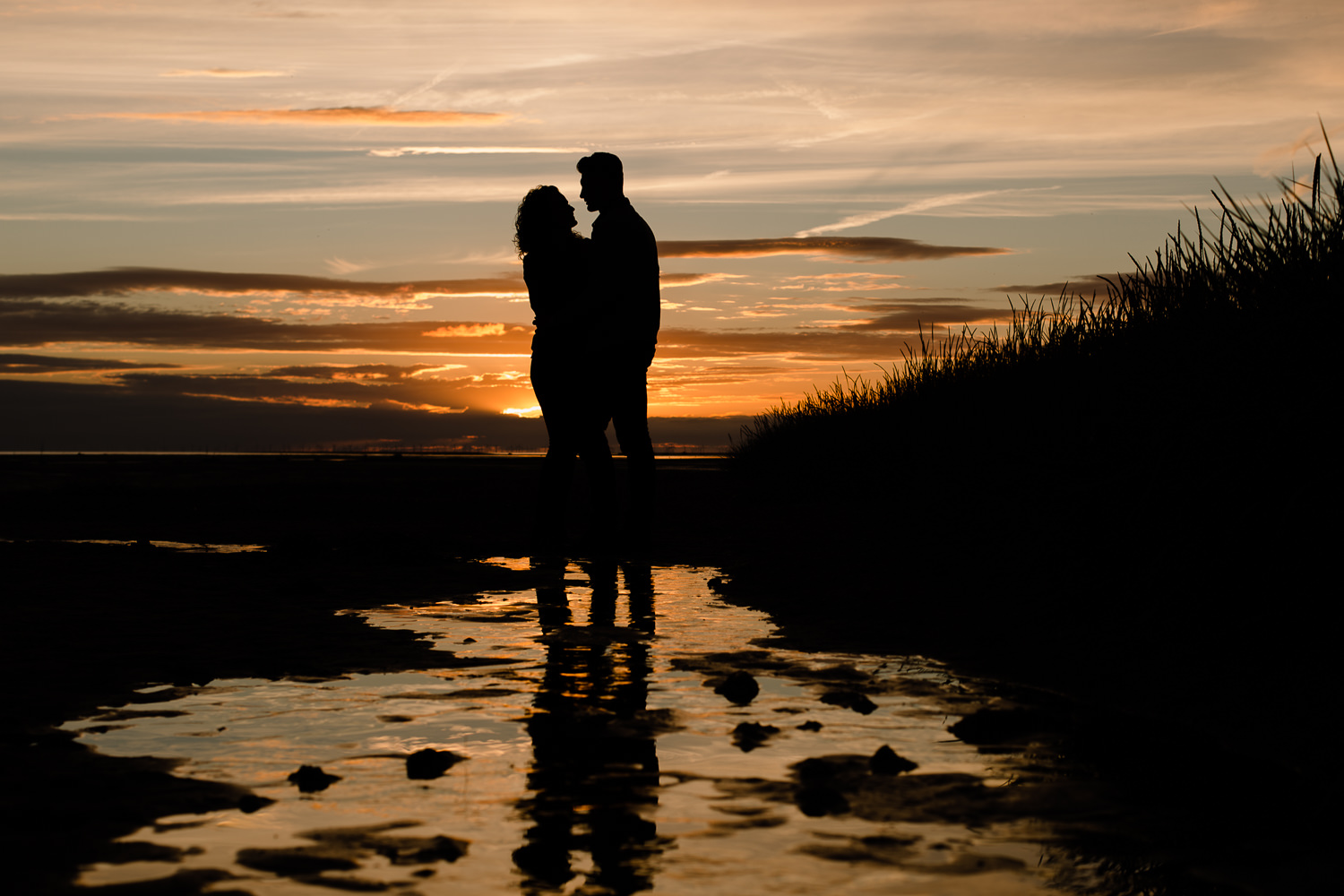 Sunset Pre Wedding Shoot, a couple silhouetted against the colourful sky and their reflection on the wet beach - Merseyside Wedding Photographers