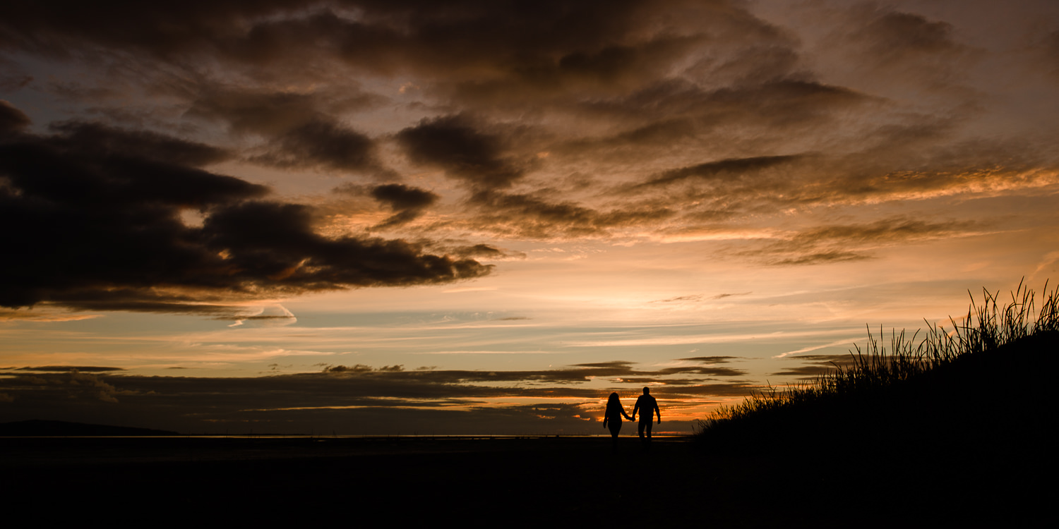 Couple walking towards the sunset, silhouetted against the sky - Merseyside