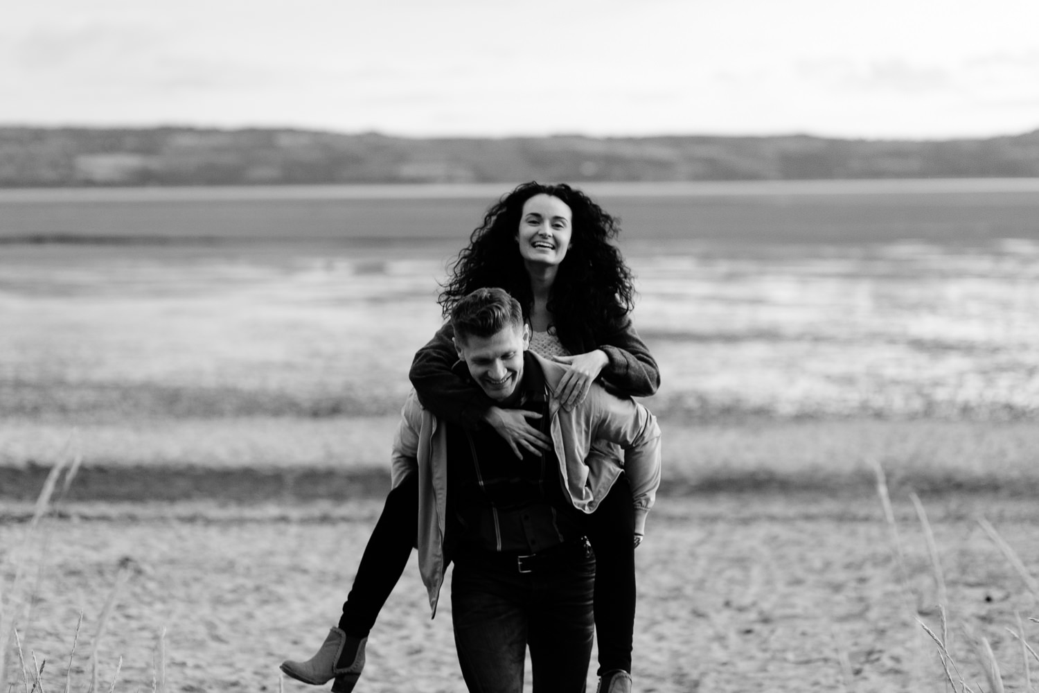 A couple piggy back on the beach in Wirral Country Park
