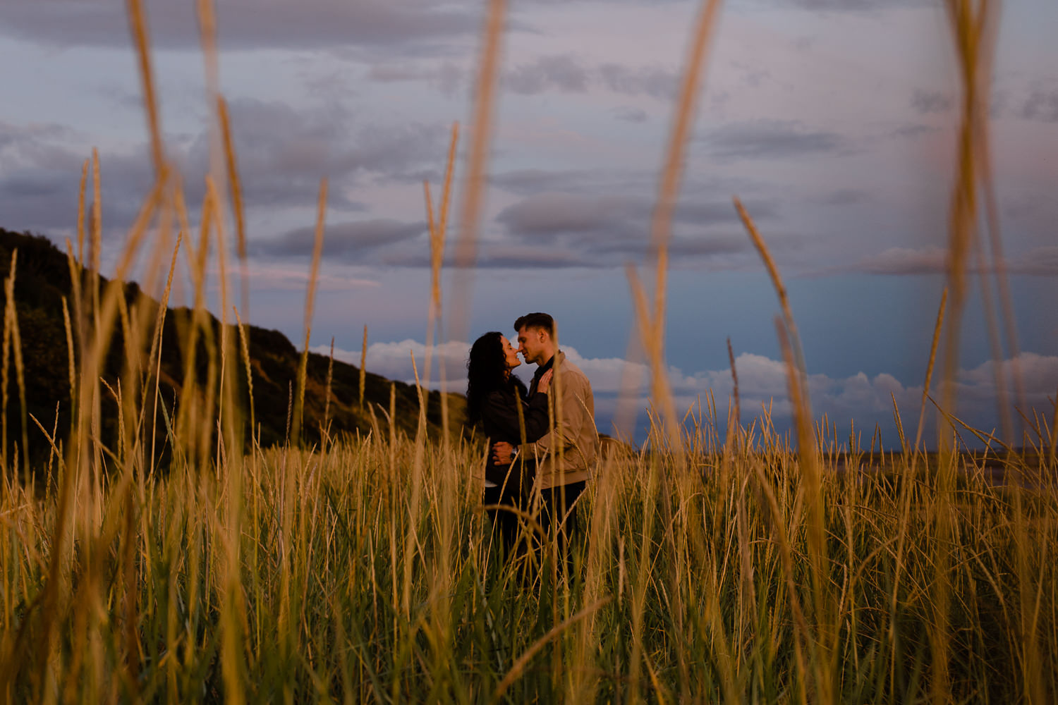 Sunset photography - Couple stood in the grass on a beach in Merseyside