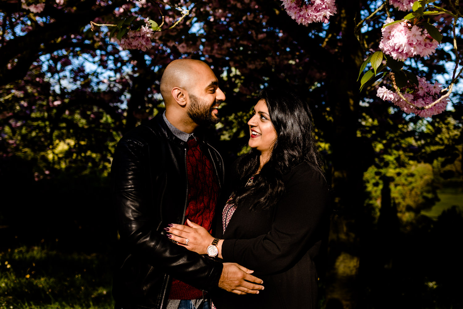 Laughing couple with a blossom tree on a pre wedding shoot.