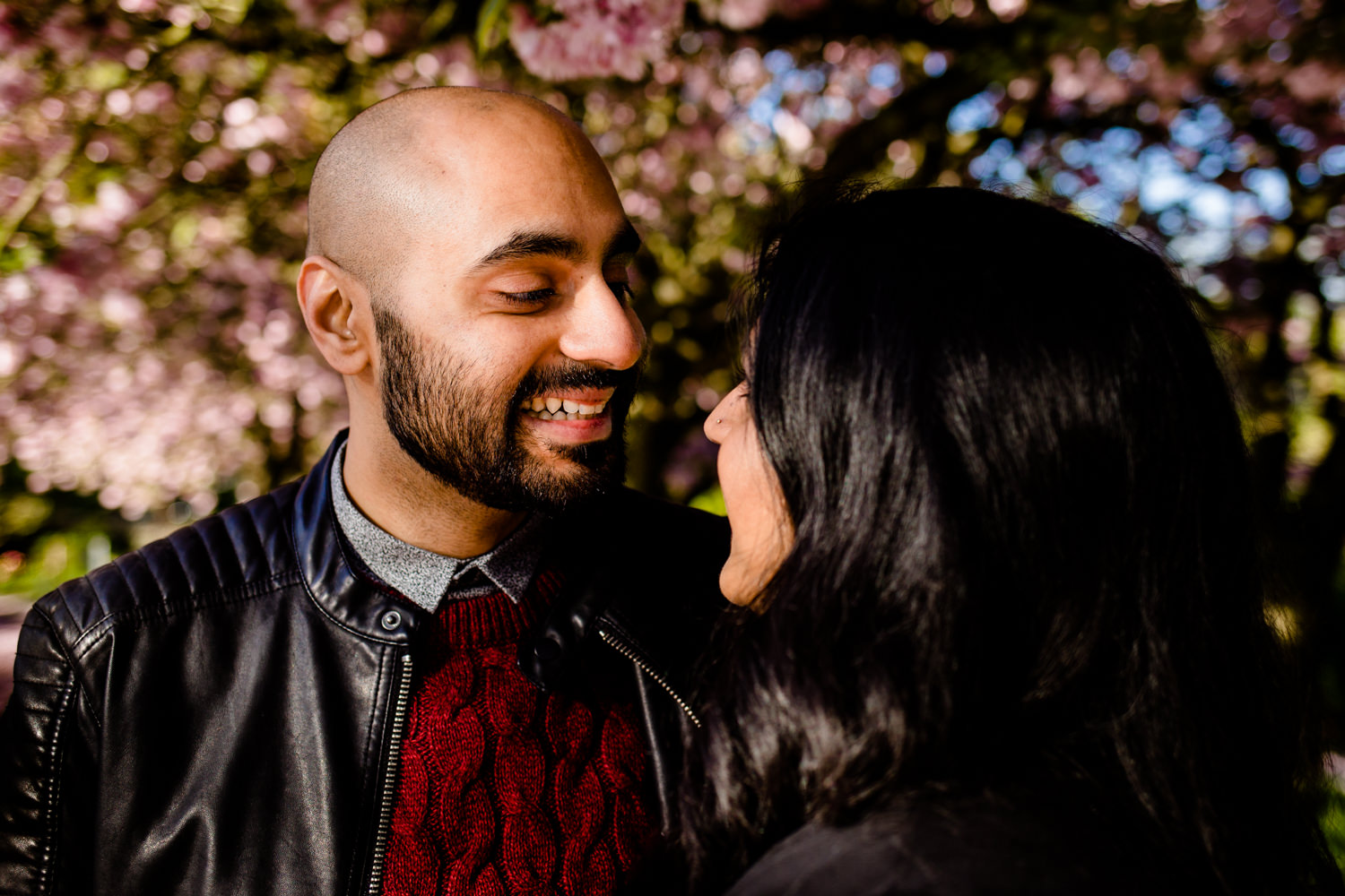 A man and woman looking at each other under a blossom tree in Manchester