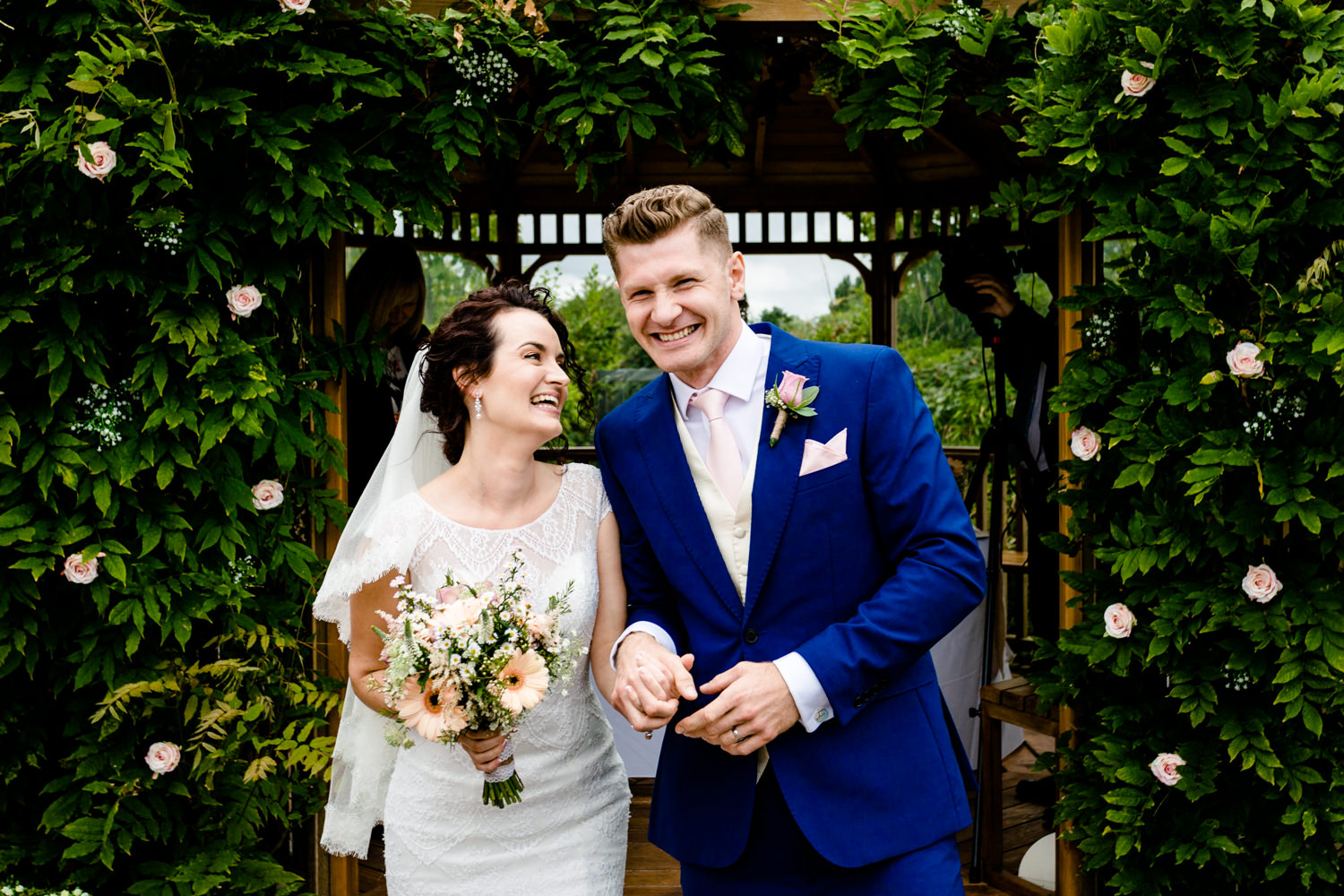 A just married couple smiling at the front of their outdoor ceremony at Pryor Hayes in Cheshire by wedding photographers Zoe & Tom