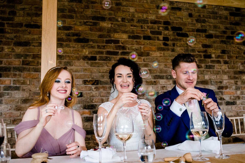 Bride, groom and birdesmaid blowing bubbles inside Pryors Hayes venue, Cheshire.