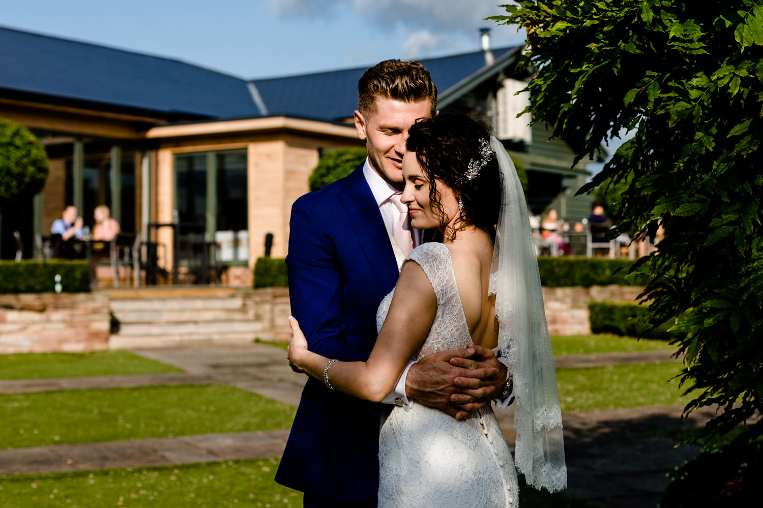 A married couple embrace in the sun at their summer wedding in Cheshire
