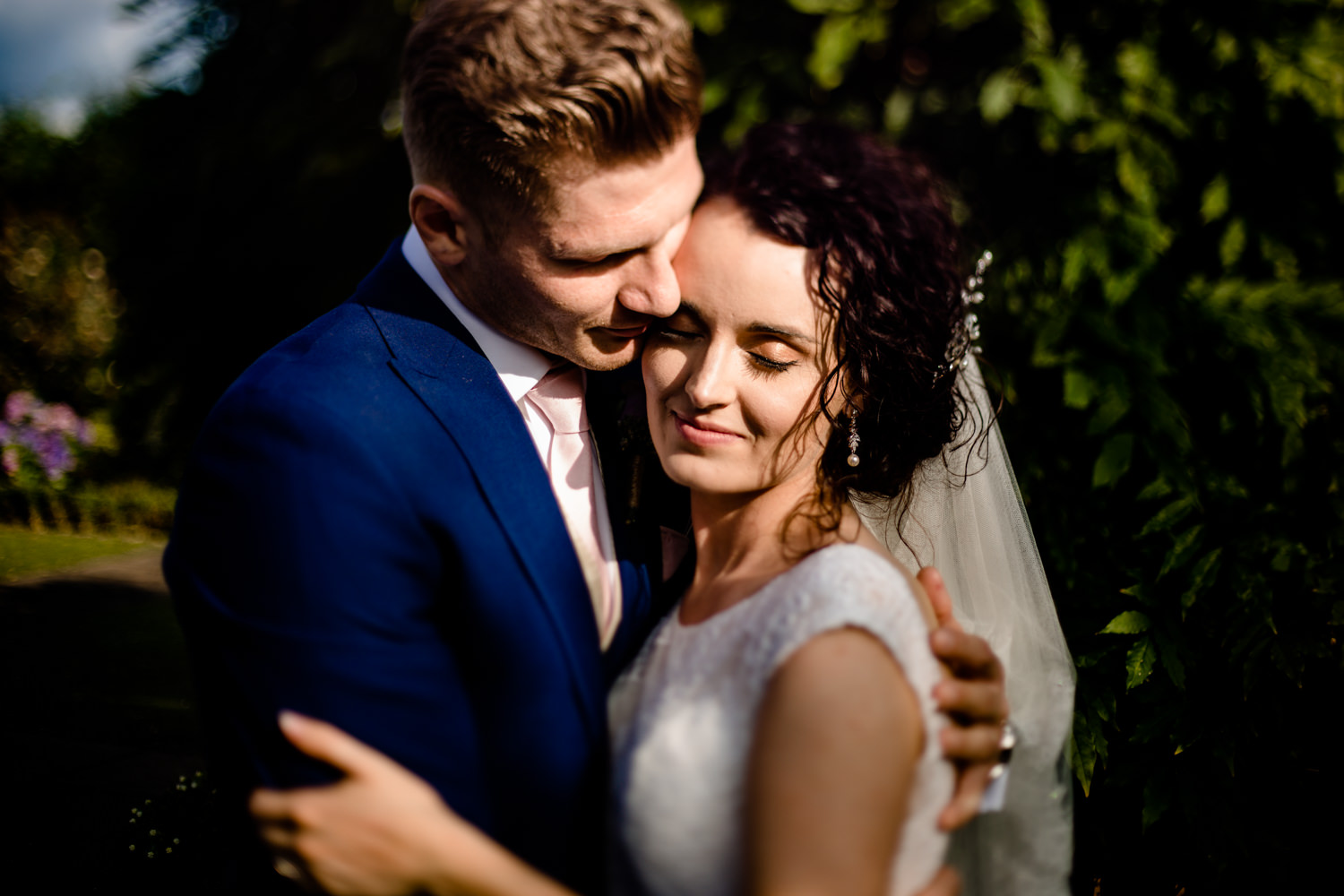 Freelens photography image of a wedding couple in a close embrace lit by golden summer sunshine at Pryor Hayes in Cheshire