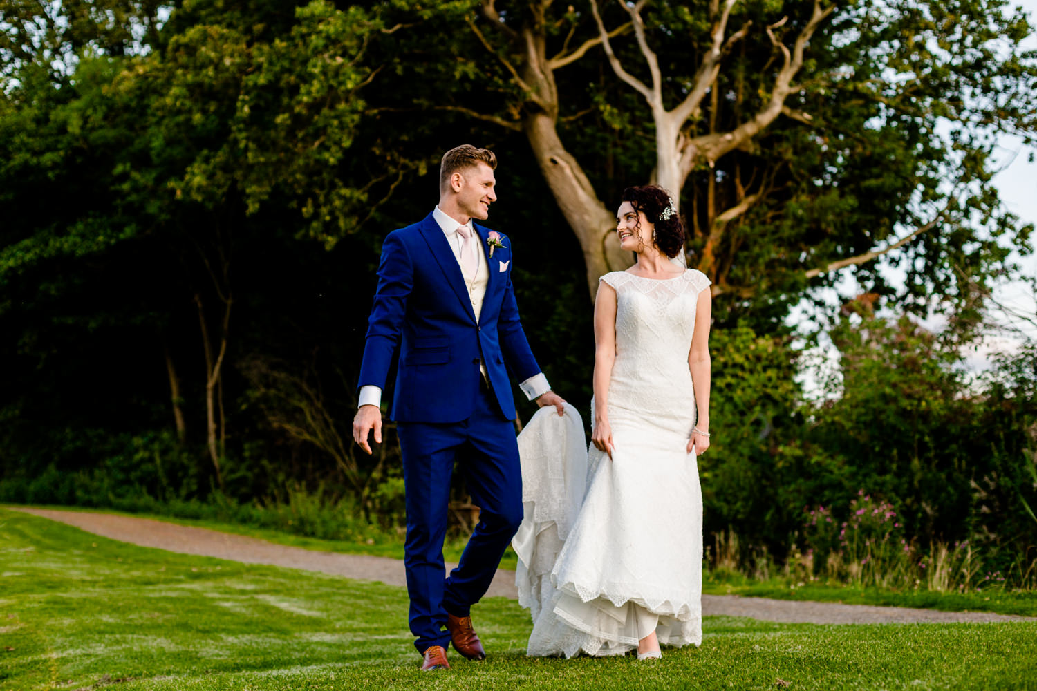 Bride and groom walk towards sunset during their golden hour shoot in Cheshire.
