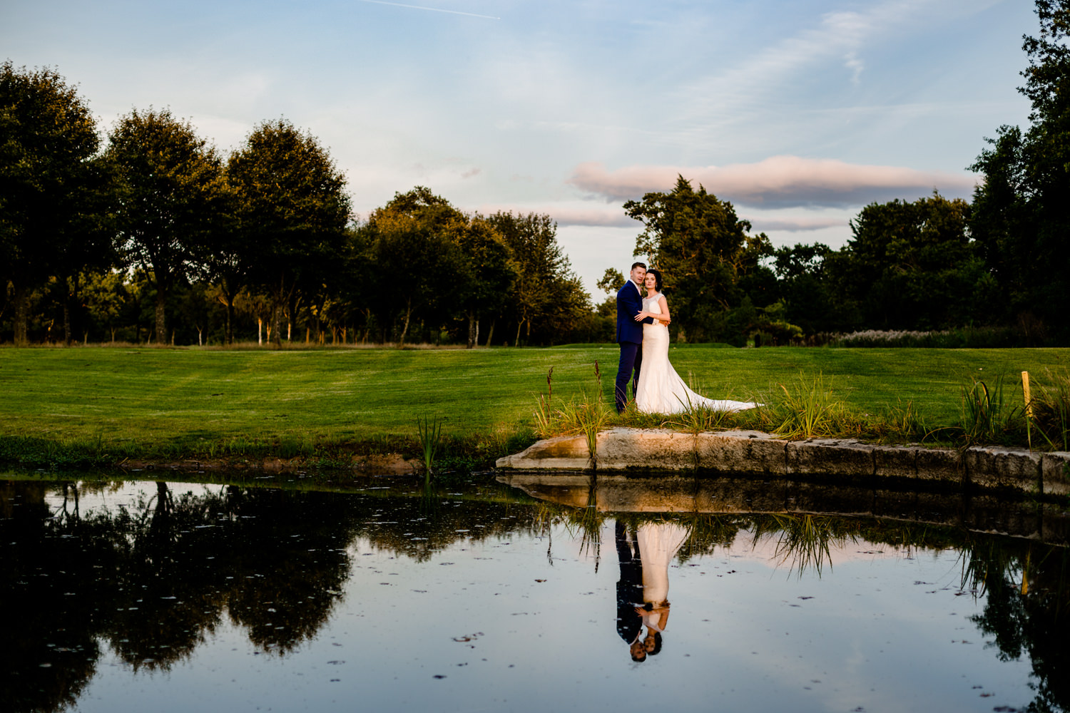 Sunset lights a bride and groom stood by a lake at Pryor Hayes, by wedding photographers in Cheshire