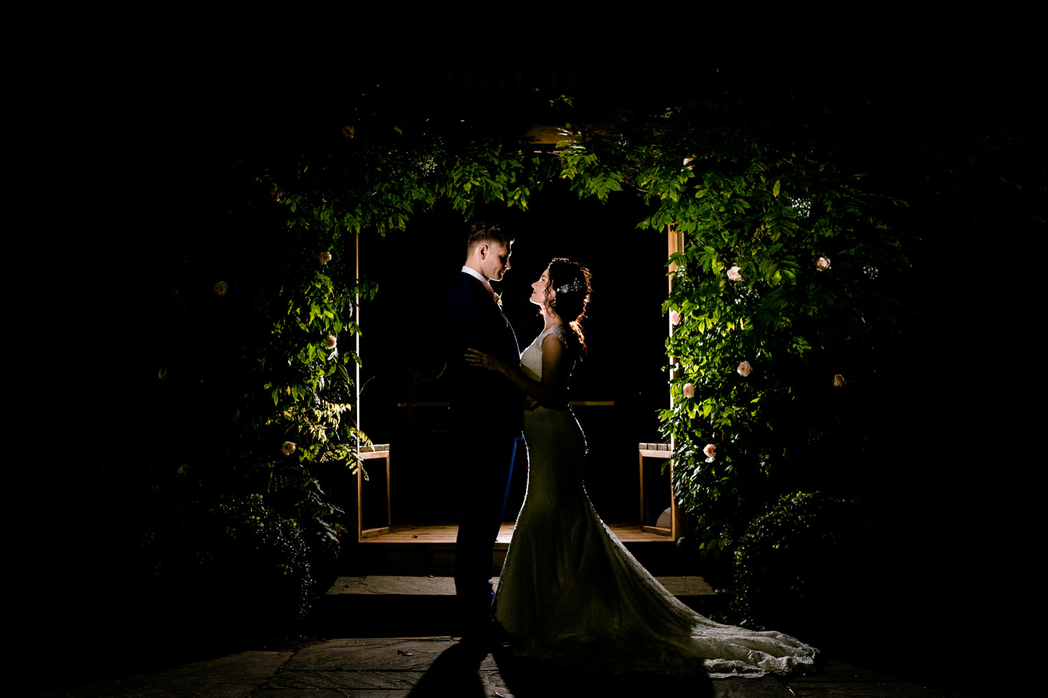 Pryors Hayes wedding venue in Cheshire, bridge and groom stood in front at the garden pagoda photographed at night.