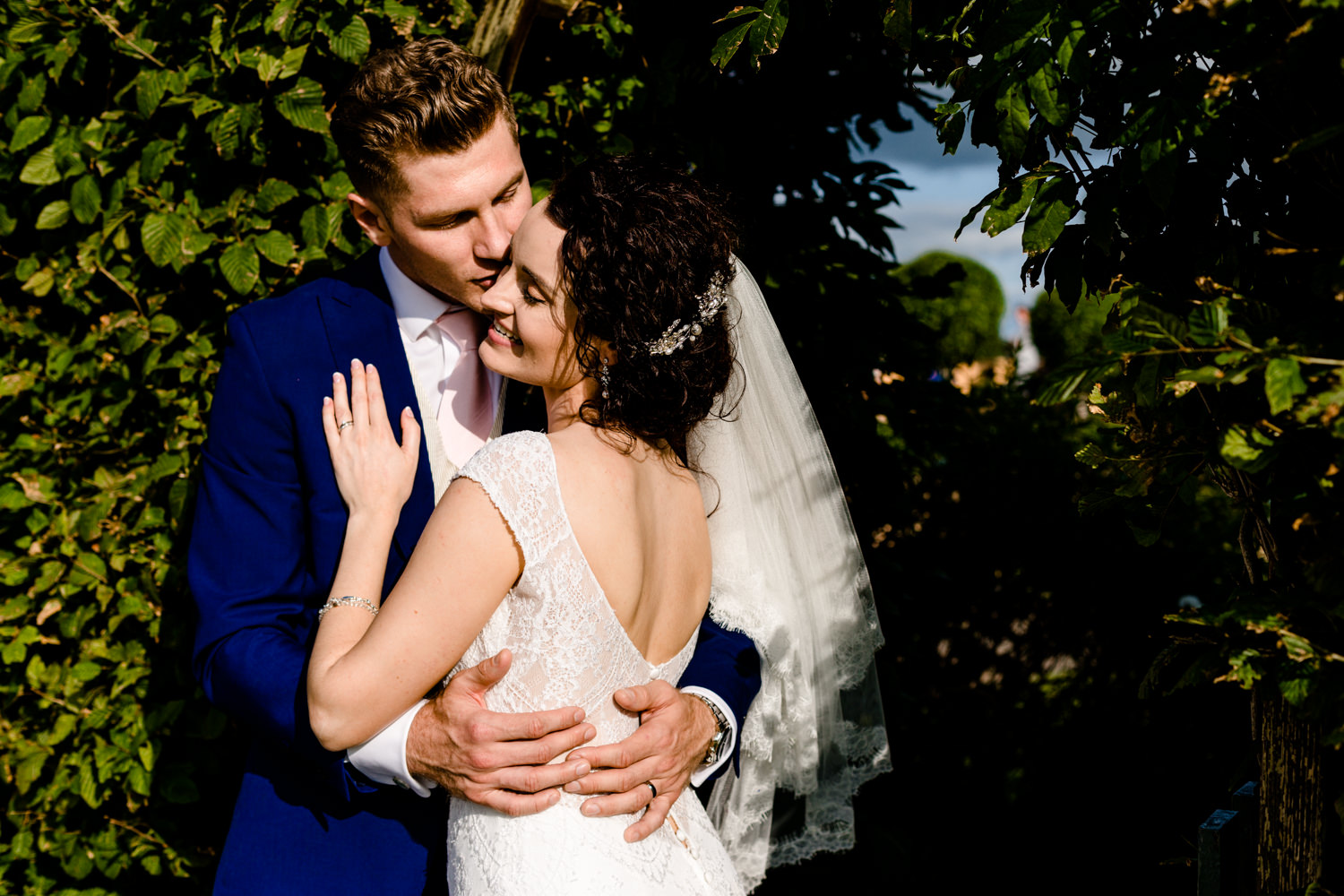 Bride and groom embrace in front of a hedge at Pryors Hayes venue.