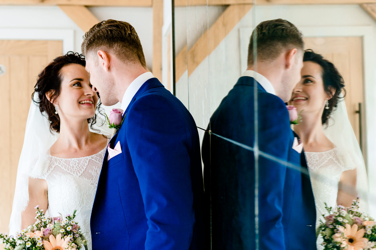 A wedding couple close together with their refection in a mirror.