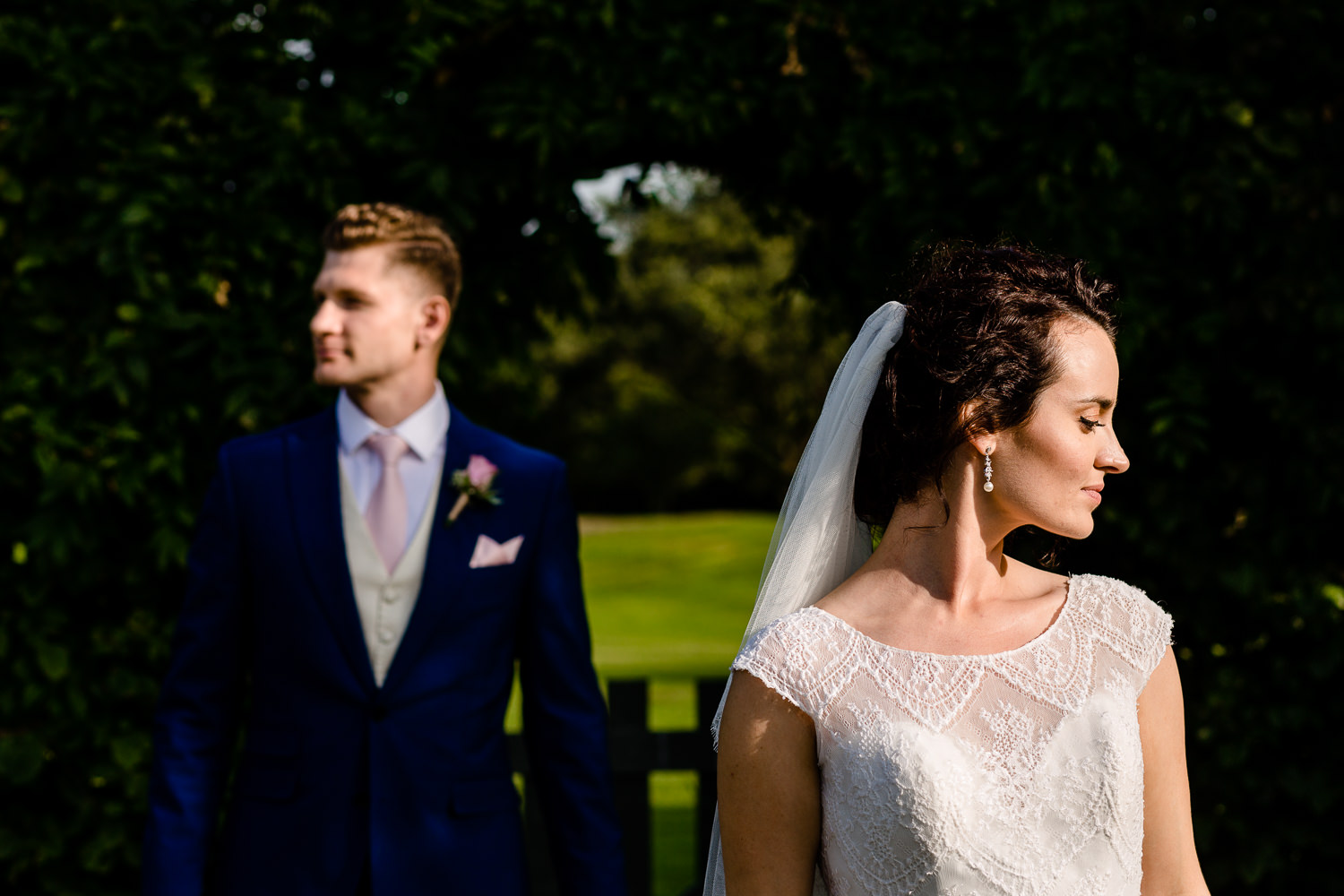 Bride and groom looking left and right at Pryors Hayes by a wedding photographer in Cheshire.