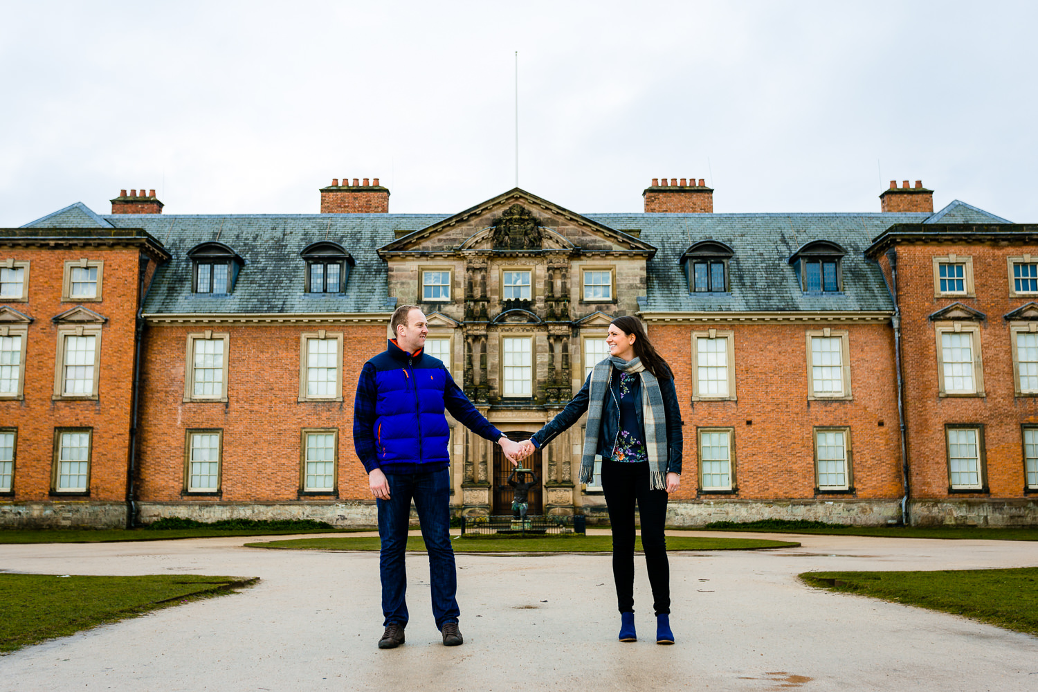 An engaged couple holding hands in front of Dunham Massey manor house.