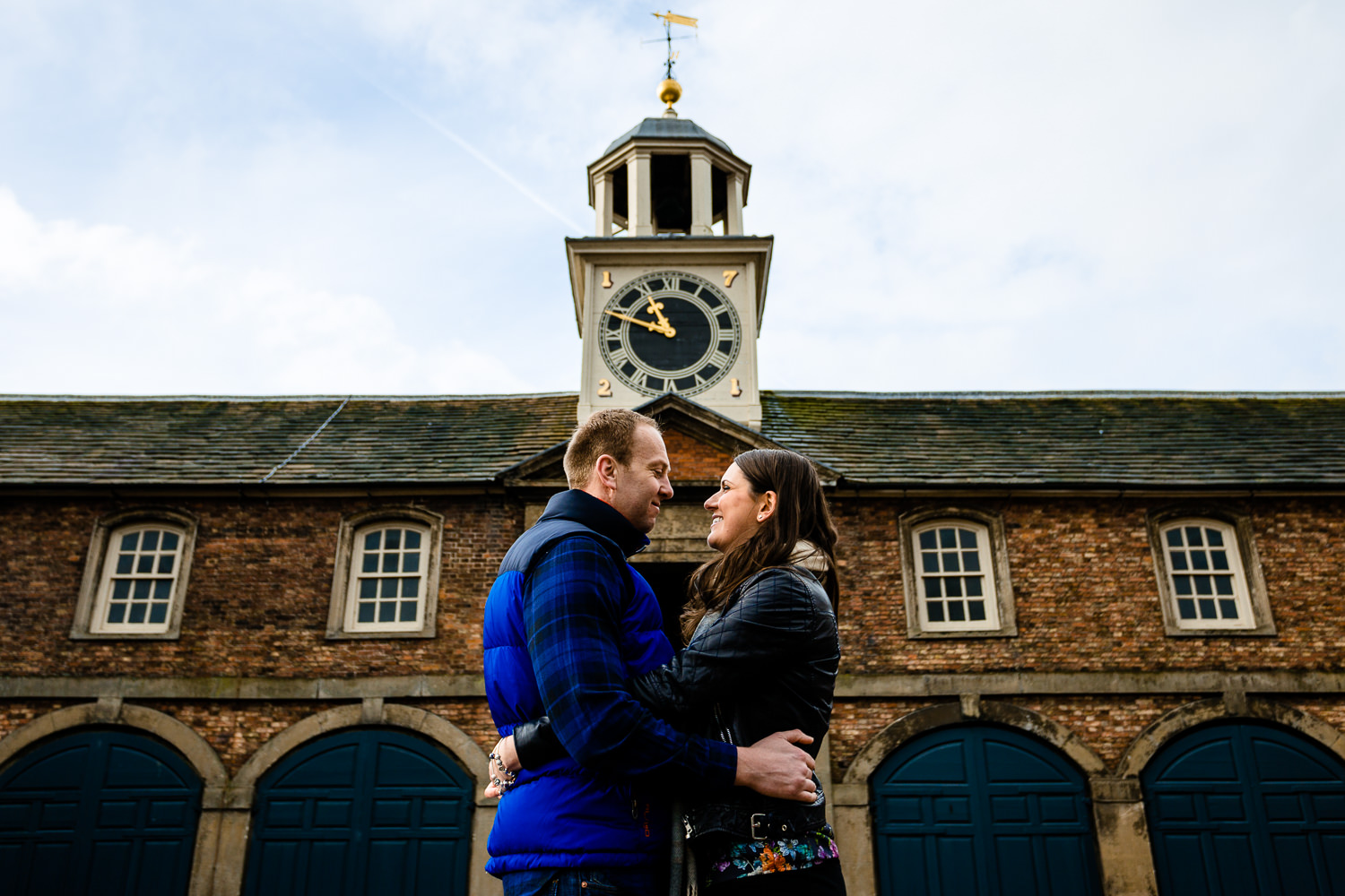 Claire & Damien cuddle in front of the clock tower at Dunham Massey on their pre wedding shoot.