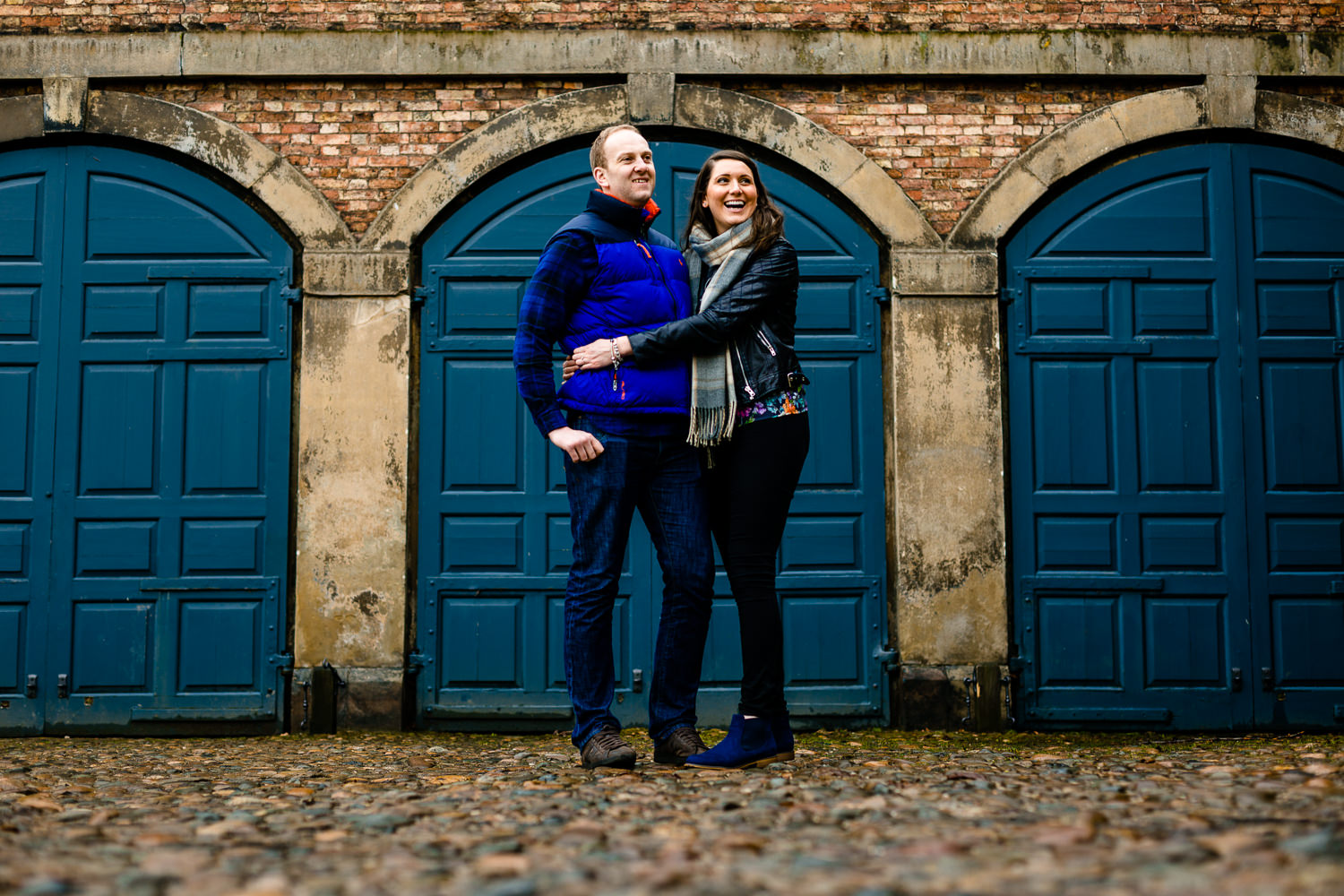 Dunham Massey pre wedding shoot, a couple laughing and cuddling in front of the blue coach house doors.