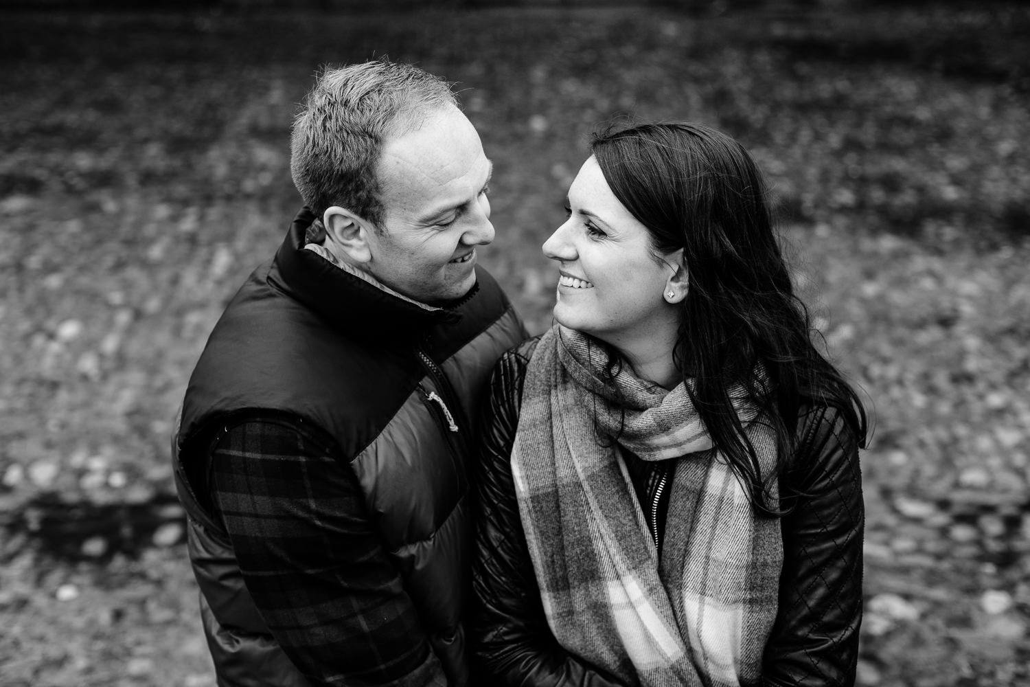 Black and white photo of a couple smiling at each other, Dunham Massey pre wedding shoot.