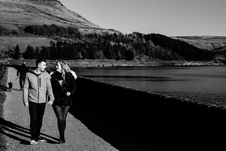 Engaged couple Sarah and Jason walking along side Dovestone reservoir.