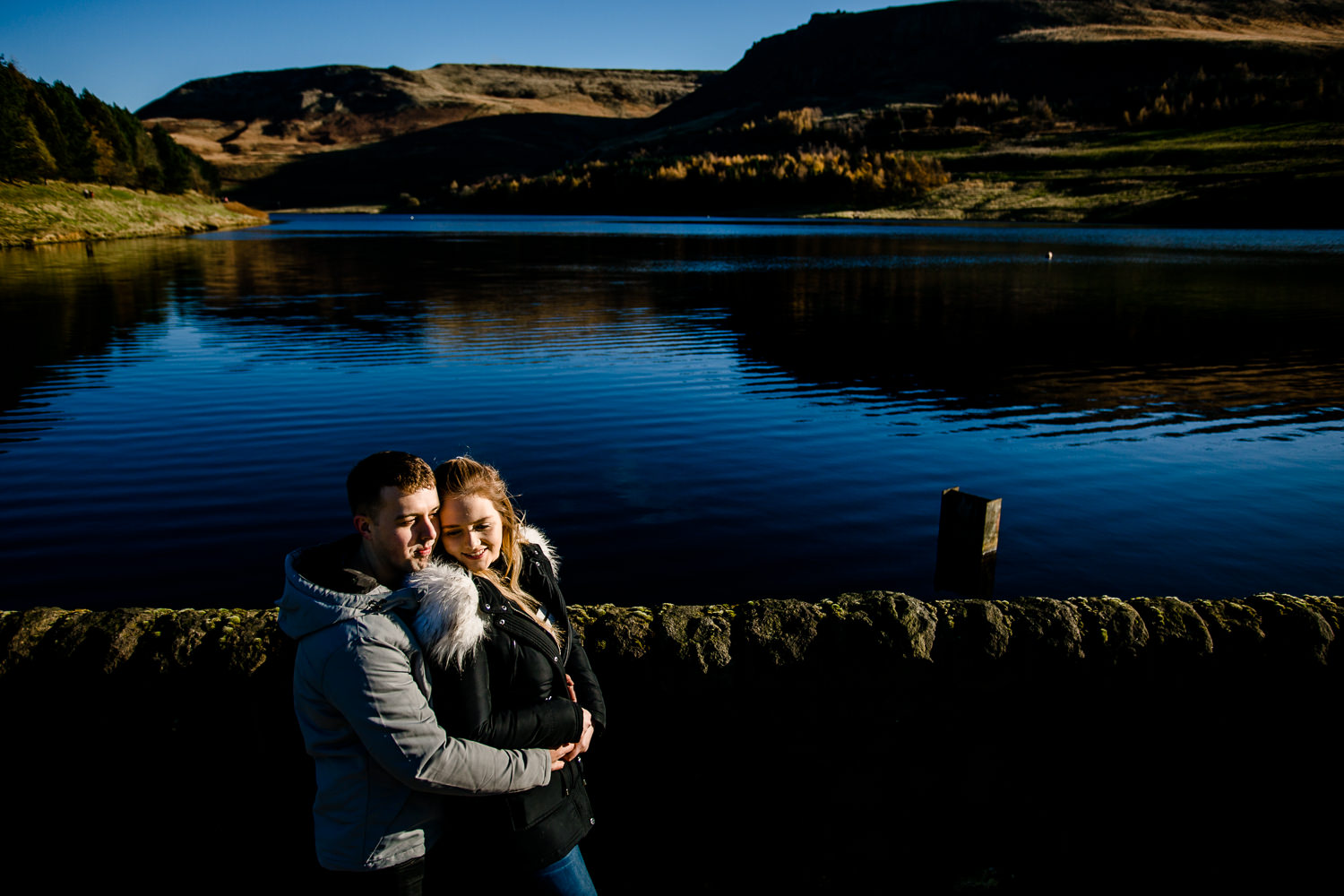 Cute couple, Sarah and Jason laughing and cuddling on their pre wedding shoot at Dovestone reservoir, by Manchester wedding photographers, Zoe & Tom.