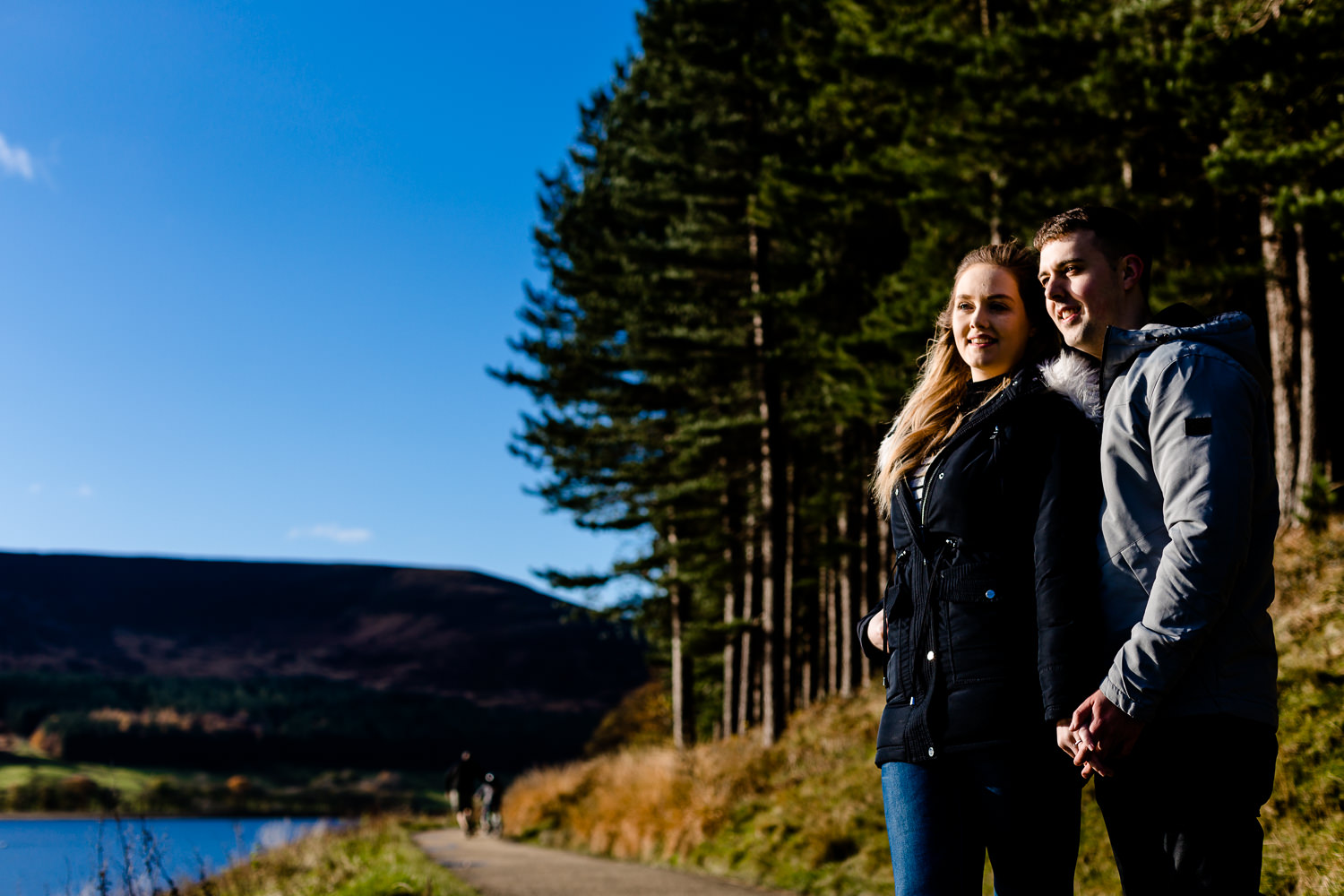 A couple stood alongside a reservoir and pine trees in Manchester.