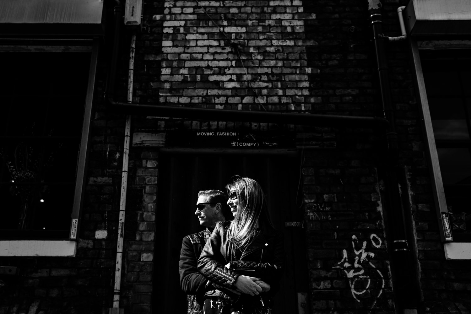 Northern Quarter pre wedding shoot manchester wedding photographers, a couple cuddle in the sunlight