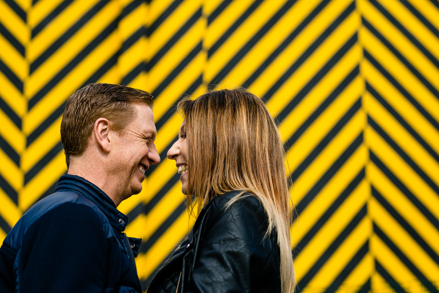 A couple laughing in front of Hacienda inspired street art in Manchester.
