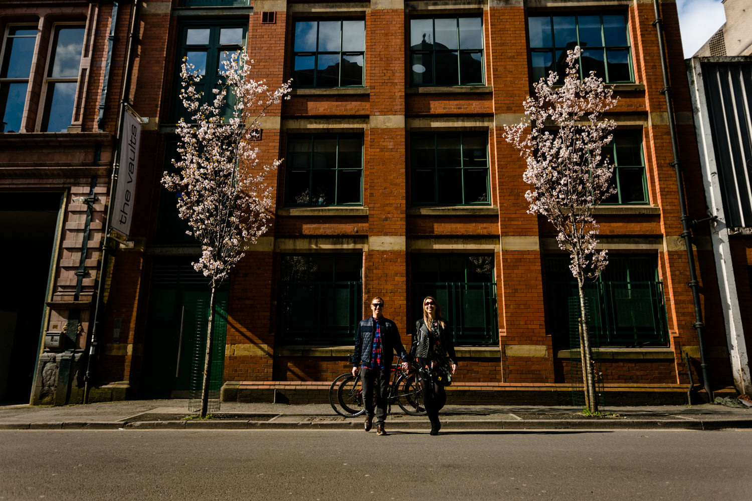 A couple cross the street in the Northern Quart of Manchester between some blossom trees.