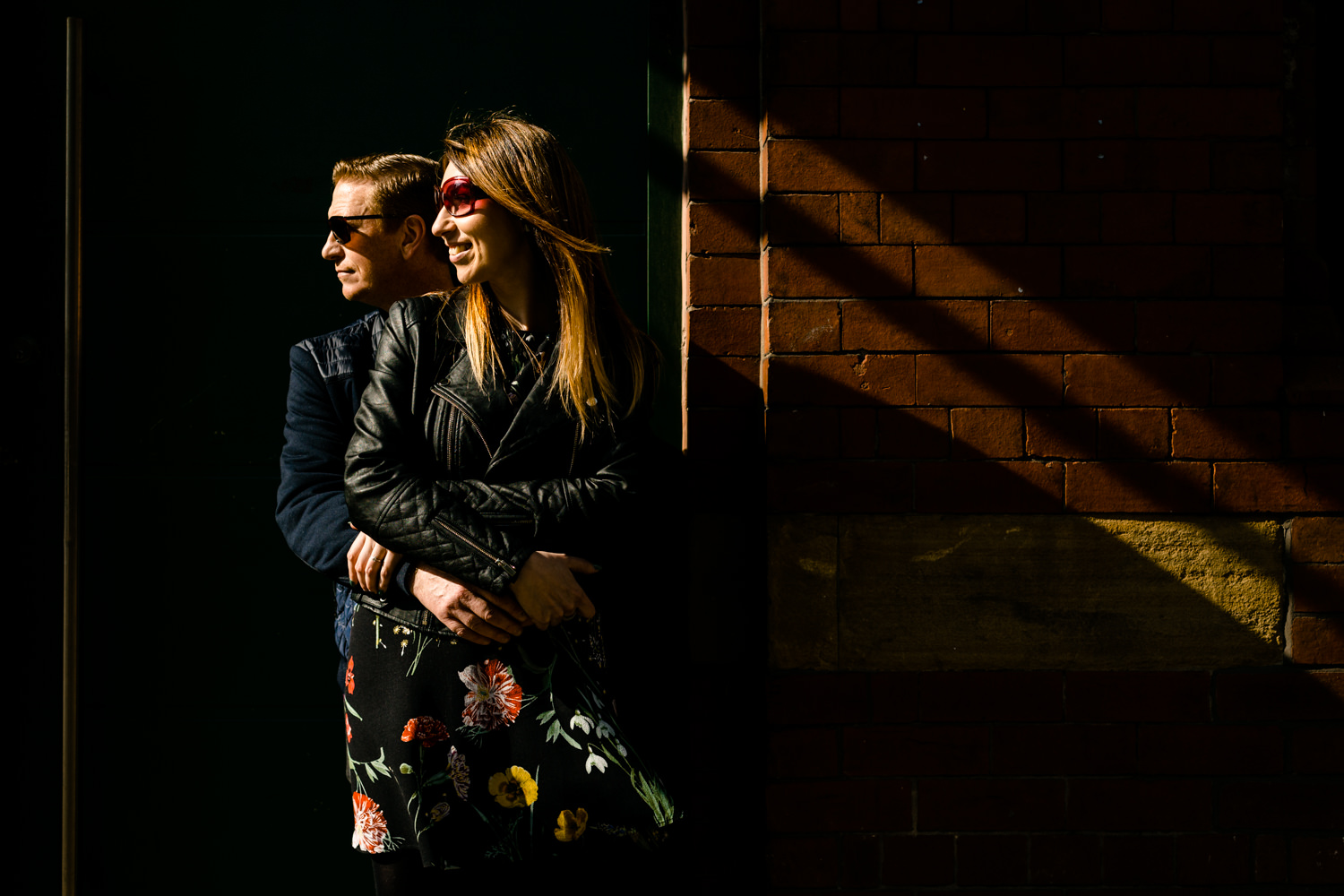 Sun shines on a cool couple in sunglasses on their Northern Quarter pre wedding shoot by Manchester wedding photographer.