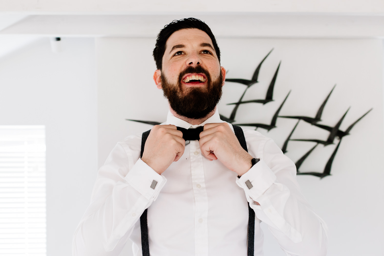 Groom straightens his tie at a Wales wedding.