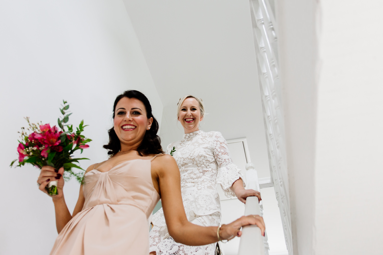 Bride and bridemaid coming down the stairs before a Wales wedding in Anglesey.