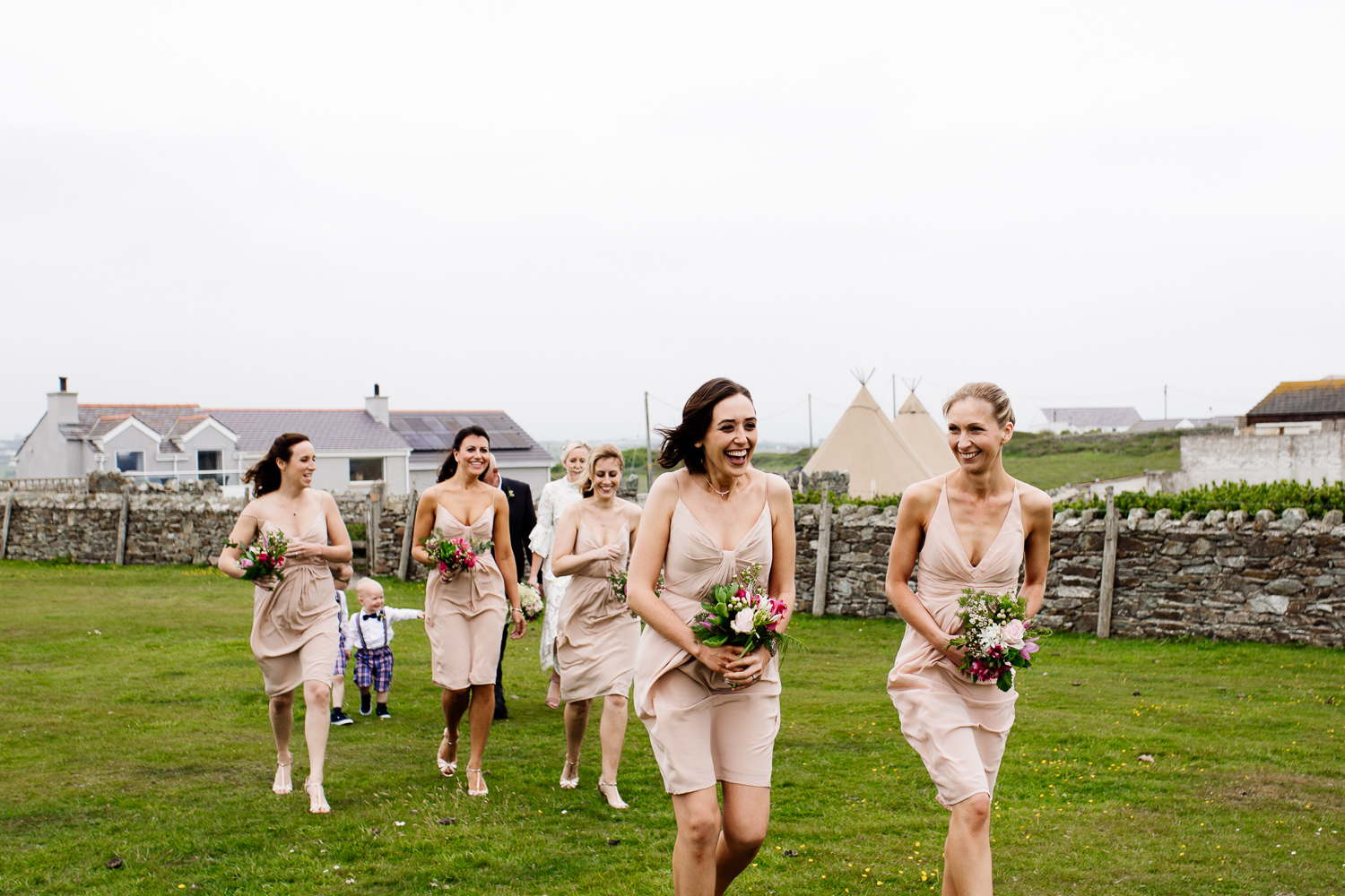 Bridemaids brave the windy headland in Anglesey, wedding photographer Wales.