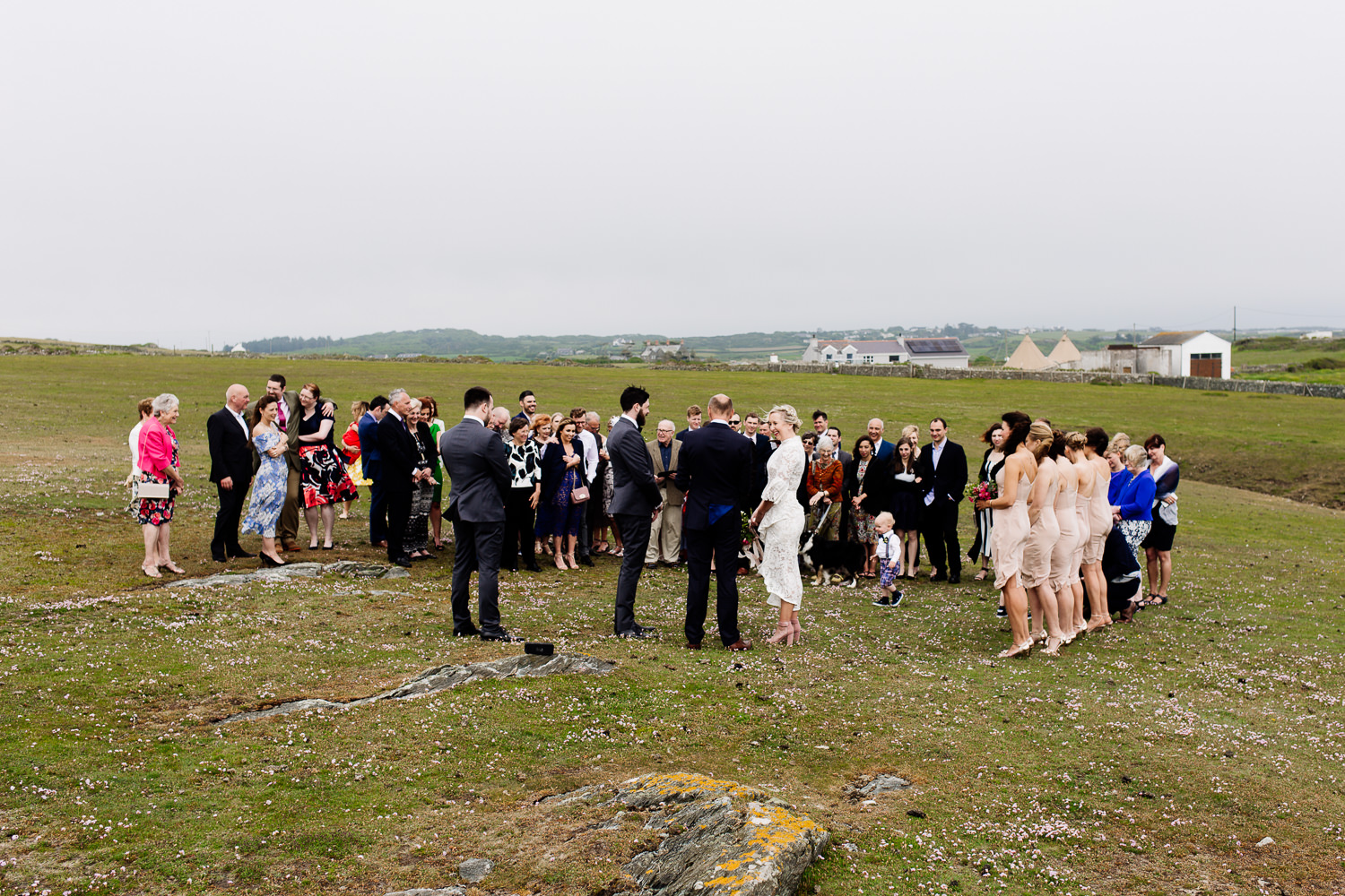 An outdoor ceremony on the headland in Anglesey at a festival theme tipi wedding by Wales wedding photographers Tom and Zoe.