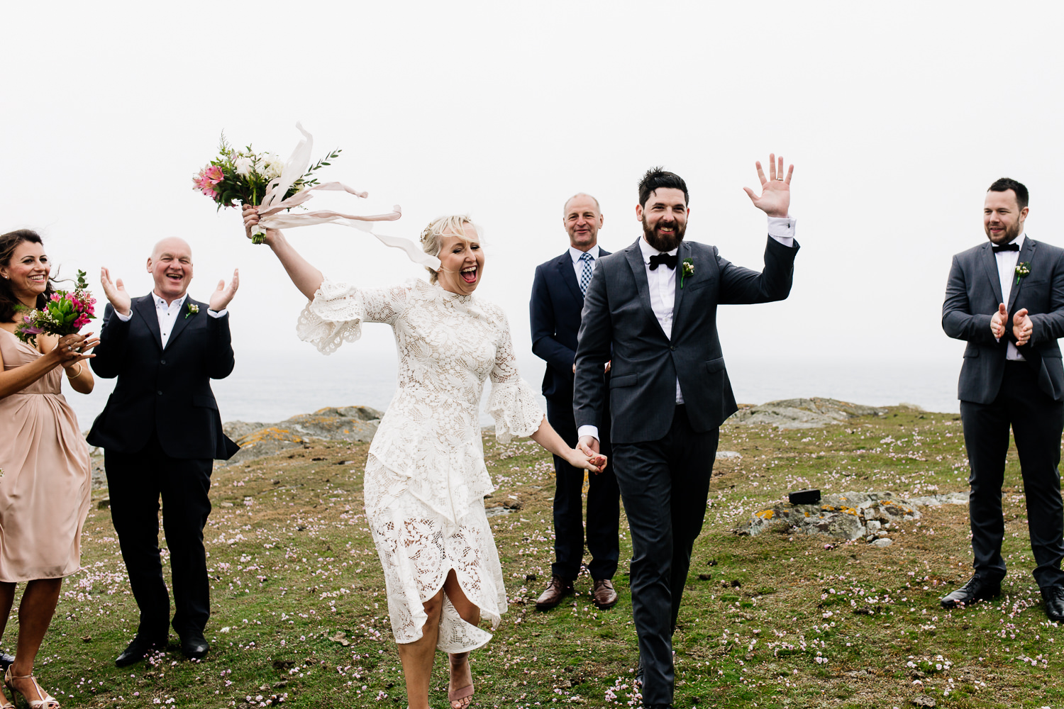 A bride and groom celebrate their wedding at an outdoor ceremony on the headland of Anglesey, Wales wedding photographers.