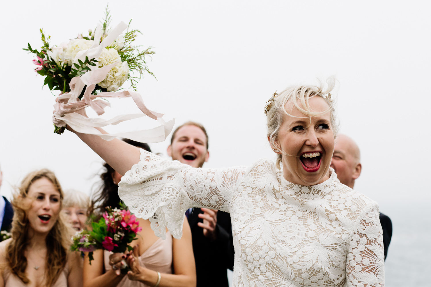 A bride celebrating getting married with her bouquet in the air a an outdoor ceremony in Anglesey, Wales.