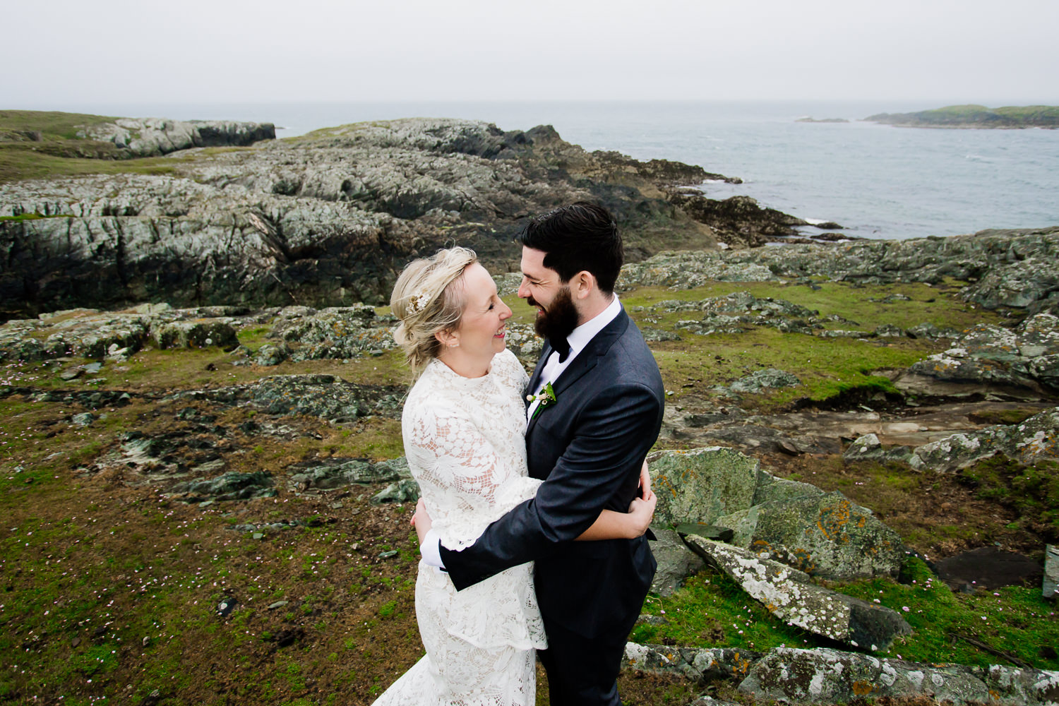 A bride and groom keeping warm on the cliffs in Anglesey, Wales.