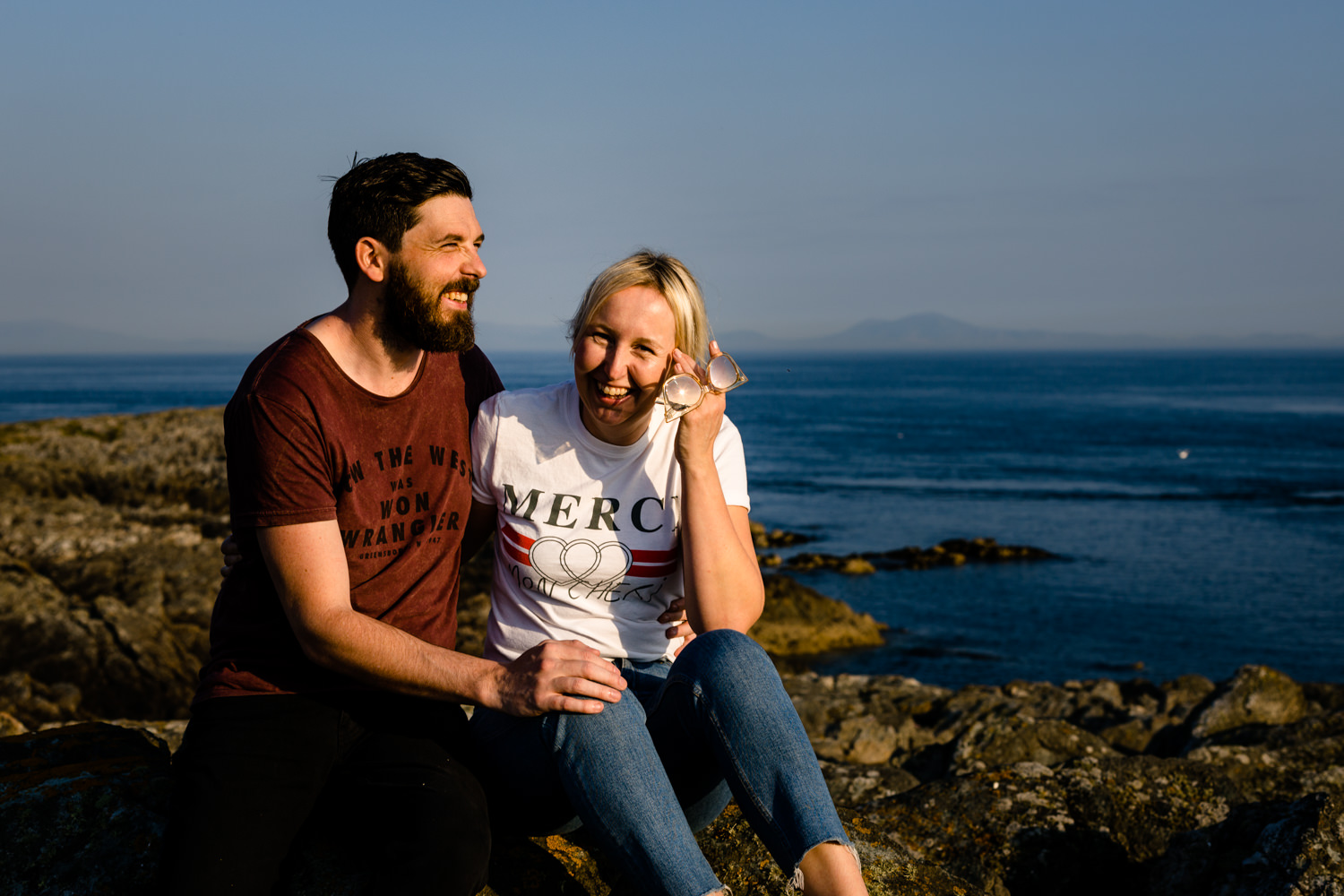 Katie & Sean sat on the rocks on the Anglesey headland, laughing together.