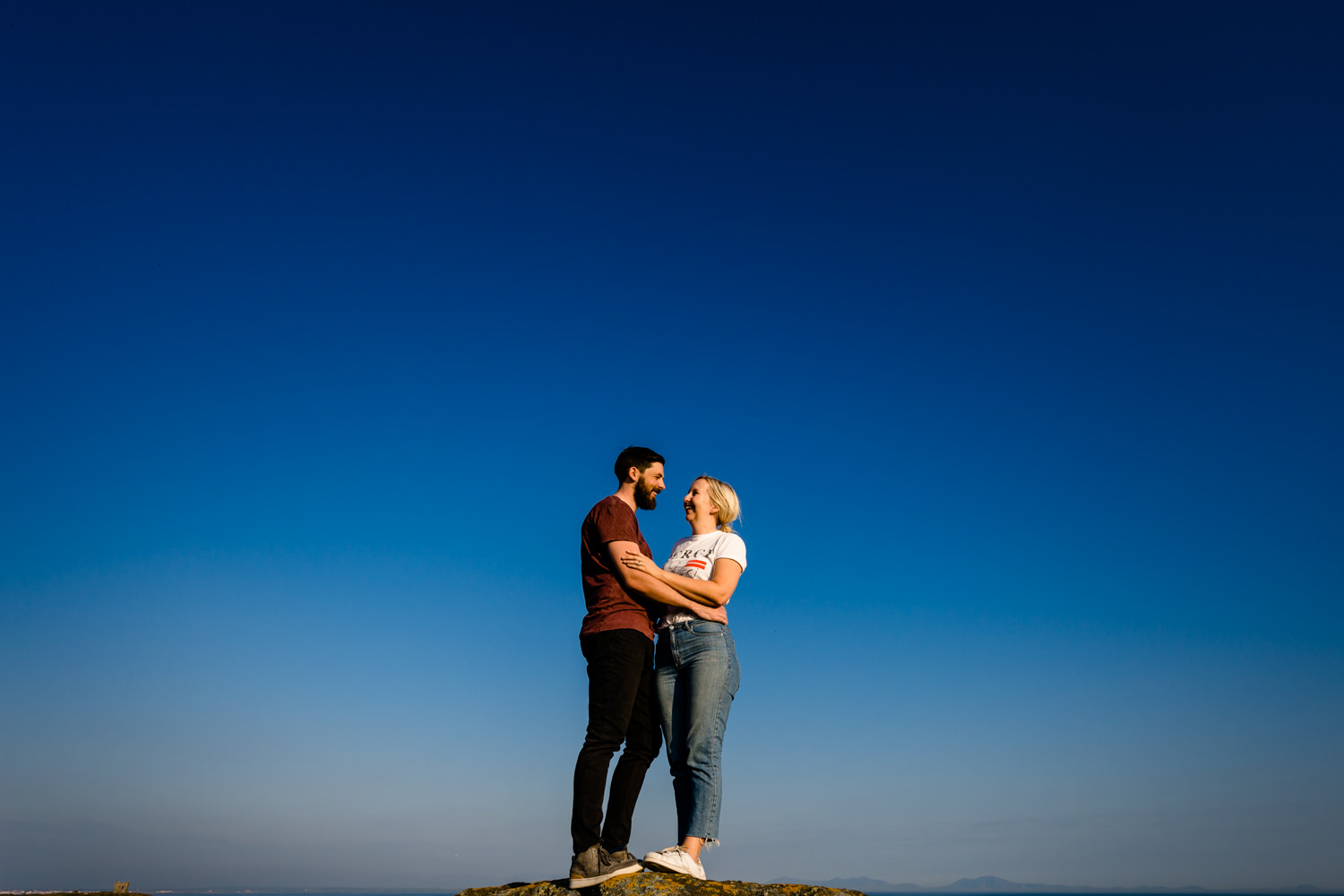 An engaged couple stood on a cliff in front of a blue sunny sky in Anglesey, Wales. By wedding photographers Zoe & Tom of About Today Photography.